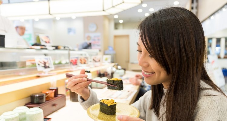 Woman eating sushi with seaweed