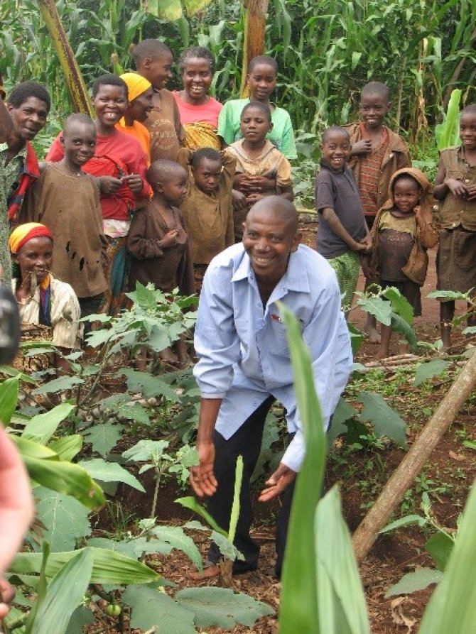 A proud motivated farmer showing his recent investment: a young improved banana tree