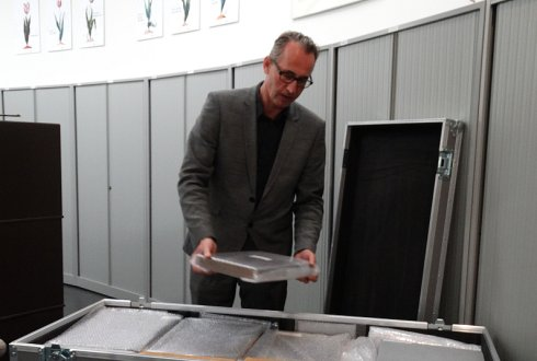 Librarian Hubert Krekels adds the last volume to a container packed with over 110 volumes.