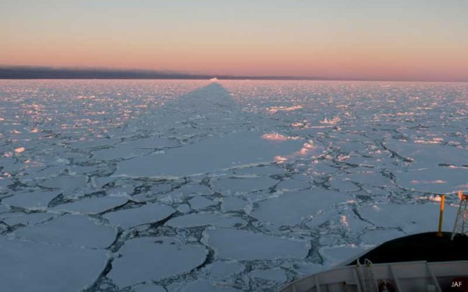 In the midnight sun, Polarstern casts it shadow over the ice to the horizon.