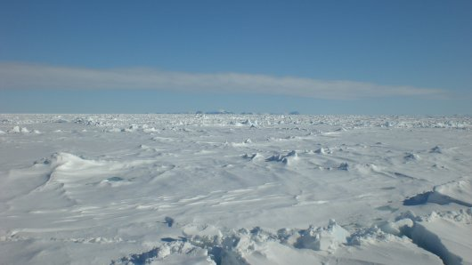 The Arctic Ocean covered with sea ice. The peaks of Svalbard are visible in the background.