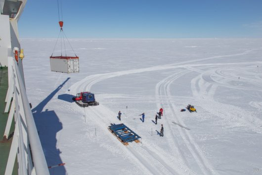 On the fast ice, dry content containers are loaded onto Pistenbully sledges, to be towed to Neumayer station.