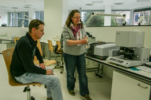 Marion Egelkraut-Holtus (Shimadzu) and Albert van Oyen (CARAT) working with an FT-IR (Fourier-Transform-InfraRed) spectrometer.