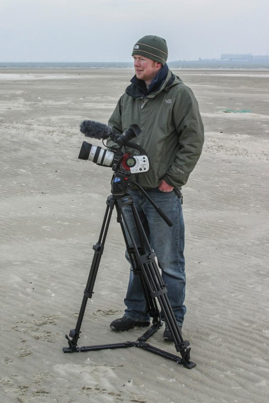 Scottish filmmaker Raymond Besant filming on the beach of Texel, the Netherlands.